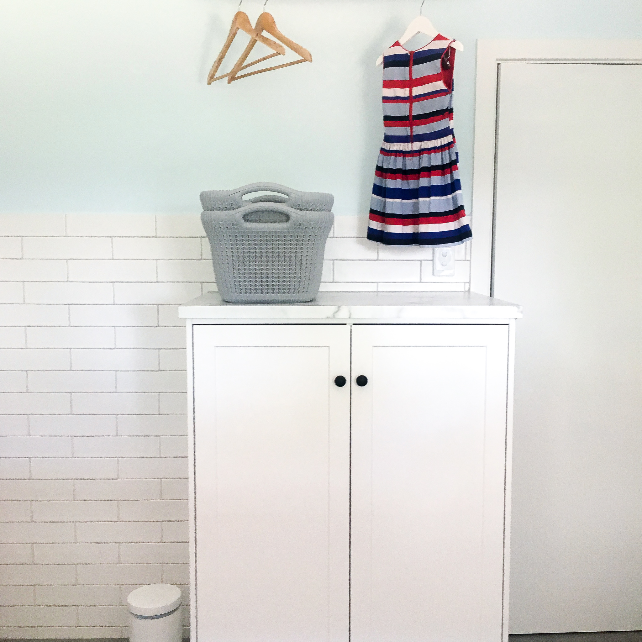 Laundry & Bathroom Renovation After: laundry sorting system hidden behind doors for when used as a guest bathroom - The Organising Bee